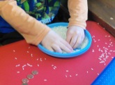 Searching to find five pennies in the dish of rice.